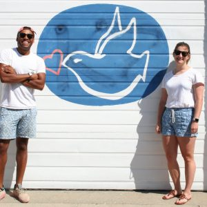 Two students stand in front of logo